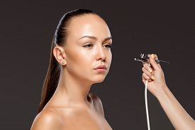 stock photo of airbrush  - visagist making makeup for model with aerograph or airbrush on black background - JPG