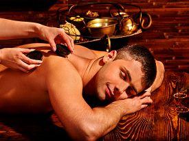 stock photo of panchakarma  - Man  having hot stones spa treatment - JPG