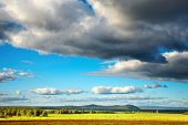 stock photo of hayfield  - Landscape with hayfield and cloudy sky - JPG