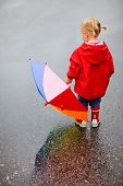 Back view of toddler girl outdoors at rainy day