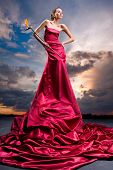 Beautiful girl in a long red dress holds an exotic flower in a hand. Against backdrop of cloudy skie