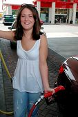pic of high-octane  - Happy and smiling girl pumping gas into vehicle - JPG