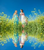 Two beautiful young girls go hand in hand. Specular reflection in the water.