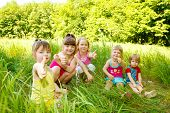 pic of happy kids  - Group of five happy kids sitting in the grass - JPG
