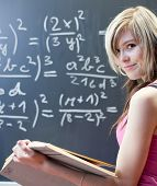 stock photo of math  - pretty young college student writing on the chalkboard - JPG