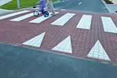 father with  a small girl on a bike crossing a street (motion blurred image)