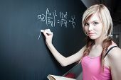 pretty young college student writing on the chalkboard/blackboard during a math class (shallow DOF;
