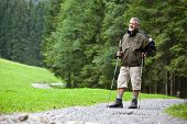 active handsome senior man stoping for a moment while nordic walking/hiking outdoors on a forest pat