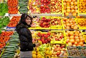 stock photo of grocery-shopping  - Beautiful young woman buying fruits and vegetables at a produce department of a supermarket - JPG