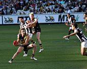 MELBOURNE - AUGUST 15: Richmond's Brett Deledio dodges Collingwood players - Collingwood vs Richmond