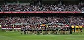 MELBOURNE - APRIL 25: Collingwood and Essendon players line up before the start of their Anzac day c