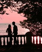 stock photo of love couple  - couple on the beach at pink sunset  - JPG