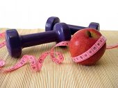 apple with measuring tape and dumbbell
