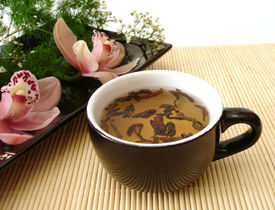 picture of black tea  - cup of tea with pink orchids on black plate over straw matt - JPG