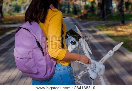 poster of Traveler  Holding Drone Quad Copter And Remote Control With Backpack In Autumn.