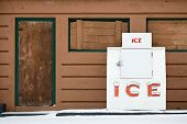 large public ice chest outdoors against old brown building and with snow in foreground.