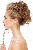 Profile of young beautiful girl with fancy stylish hairdo and candy cane in hand, over white backgro
