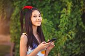 Happy Young Asian Woman With Smartphone Standing Outdoors In City Park. . Young Asian Casual Girl Us poster