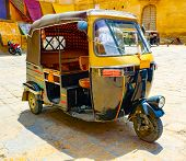Traditional Back And Yellow Motorized Rickshaw In A Jaisalmer Square, Rajasthan, India poster