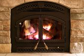 stock photo of cozy hearth  - A crackling fire in the firebox with Brick hearth - JPG