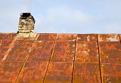 Rusty Roof Tin And Ramshackle Brick Chimney.
