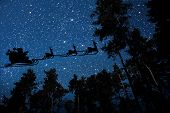 silhouette of a flying goth santa claus against the background of the night sky.  poster