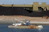stock photo of coal barge  - Coal storage factory reconstructing rock breakwall using crane on barge - JPG