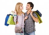 Cheerful young couple with shopping bags, isolated on white background