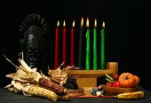 foto of humility  - Kwanza display with symbolic candles unity cup mat food corn and tribal mask - JPG