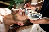 Man getting a mud mask at a spa poster