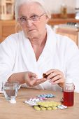 Unhappy elderly lady taking her medication