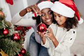 Smiling African American Woman In Santa Claus Hat Helping Daughter To Decorate Christmas Tree At Hom poster
