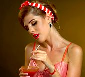 Pin up girl drink bloody Mary cocktail through straw. Pin-up retro female style. Girl wearing red dr poster