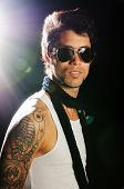 Portrait of young male fashion model with arm tattoo and sunglasses