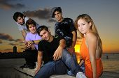 Portrait of young hispanic trendy team posing outdoors at sunset
