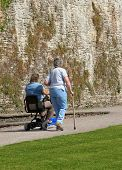 Two disabled females, one sitting on an electric mobility scooter and the other walking alongside with a walking stick. Grass lawn to the foreground and an old stone wall to the rear.