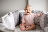 Funny Laughing Baby In A Pink Bodysuit, Sits In A White Round Crib, Around Light Pillows poster