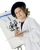 picture of french beret  - A serious elementary girl kneeling as she paints on an easel in her French beret and white smock - JPG
