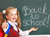 Happy child with backpack writting on blackboard.