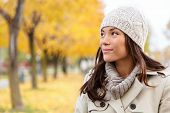 Fall woman portrait of woman looking sideways smiling serene. Beautiful young multiracial woman walk