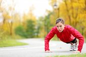woman doing push-ups during outdoor cross training workout. Beautiful young and fit fitness