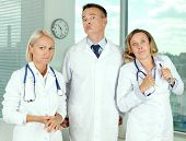 Three clinicians in white coats looking angrily at camera
