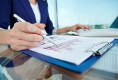 Business lady with pen pointing at document