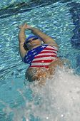 Female athlete swimming in backstroke during a pool race