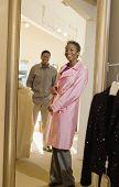 Mujer afroamericana feliz intentando sobretodo con hombre mirarla en tienda