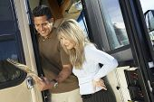 Happy couple at the entrance door of RV reading brochure