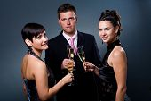 stock photo of alcoholic beverage  - Three people drinking champagne on a party - JPG
