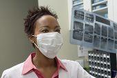 Dentista feminina olhando por cima do raio x do dente de um paciente