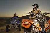 Two quad bike racers sitting on their bike