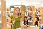 Female teenager student leaving high-school library smiling